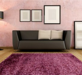 Fioletowy dywan shaggy w salonie, kanapa, lampka i kilka drobiazgów