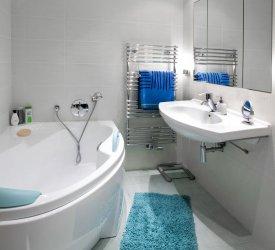 Niebieski dywanik w łazience, wanna narożna, grzejnik łazienkowy i umywalka